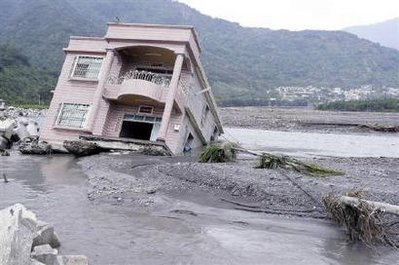 A destroyed home lies partially submerged in a river in Gaushu ...